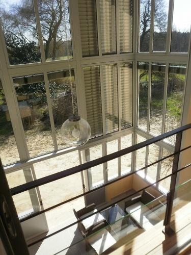 Rénovation d'une ferme avec véranda : vue depuis l'étage sur la véranda